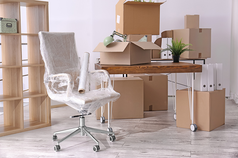 Office furniture and cardboard boxes with stuff in room. Office move concept.