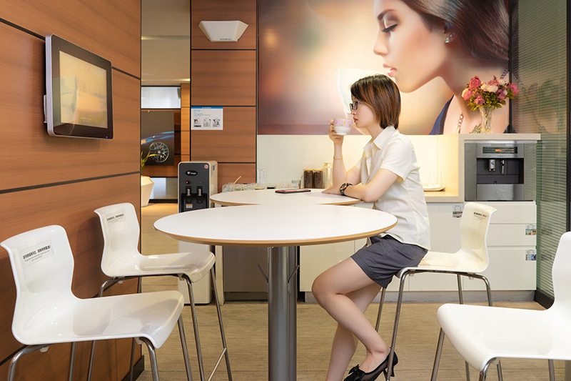 Woman drinking coffee in office pantry