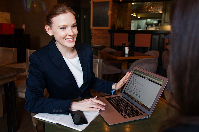 Happy business woman holding her laptop