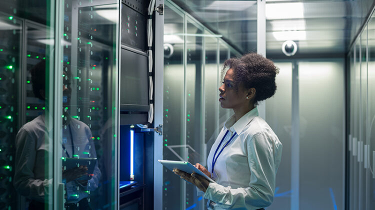 Female technician working on a tablet in a data center full of rack servers running diagnostics and maintenance on the system