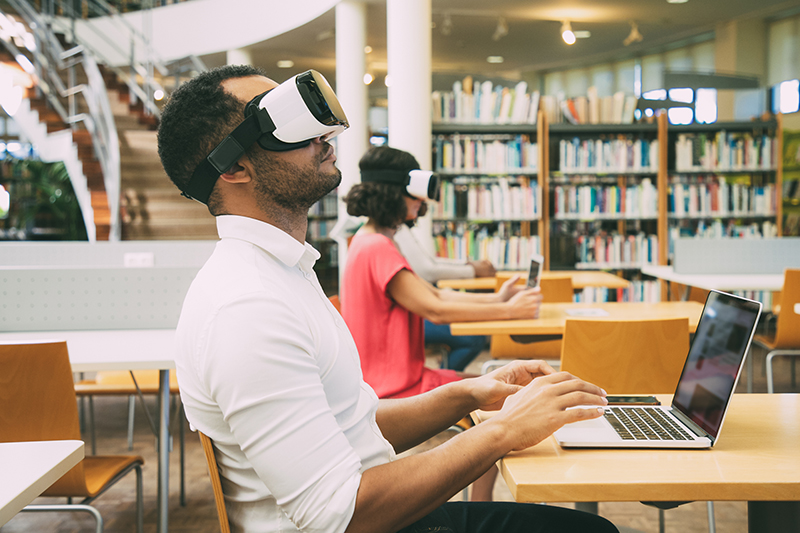 Male student training with VR simulator in library.