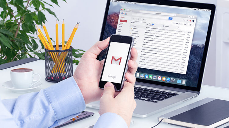 Man holding smartphone with Gmail icon on screen