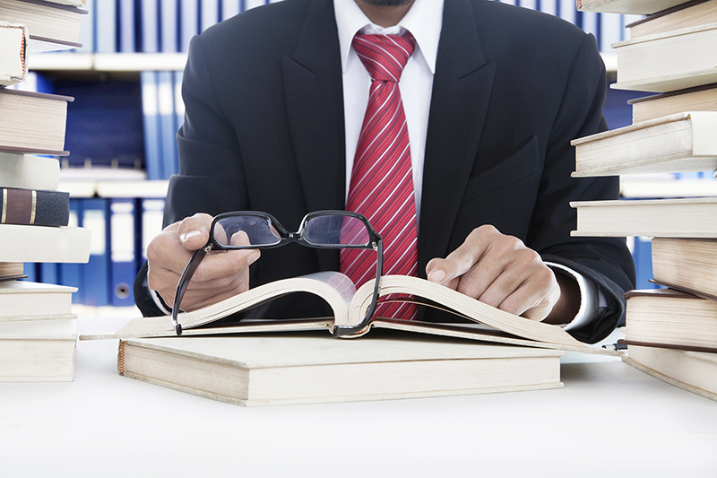 Businessman holding glasses and while reading business books