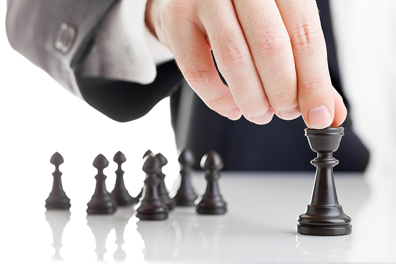 Business man moving chess figure with team behind - strategy, management or leadership concept