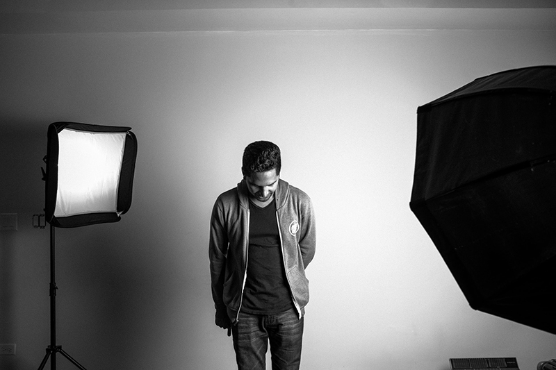 Grayscale photography of man standing in studio