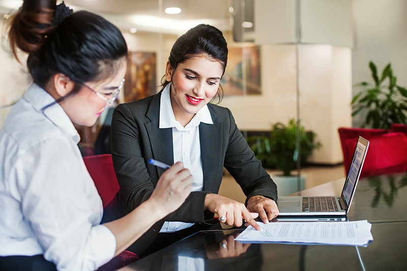 Indian female bank agent helping client sign the application document