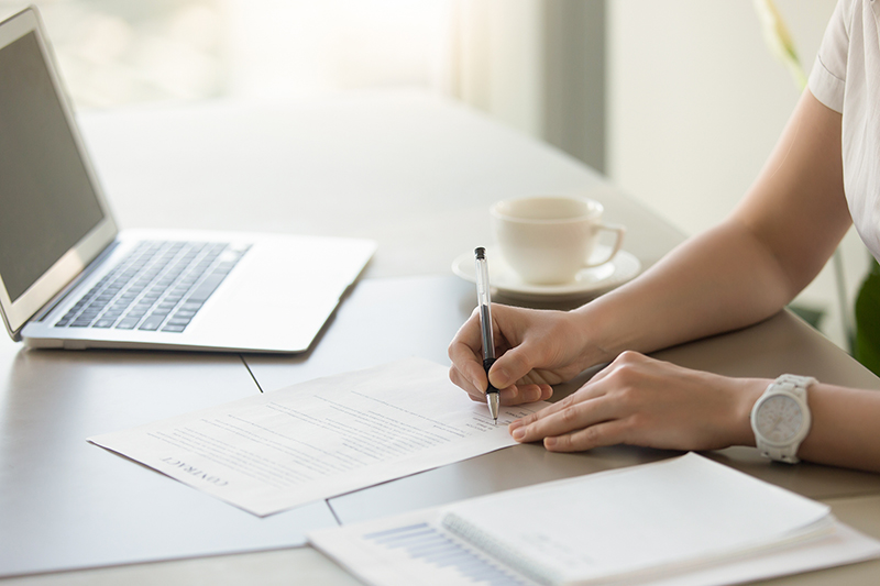 Businesswoman signing paper at workplace