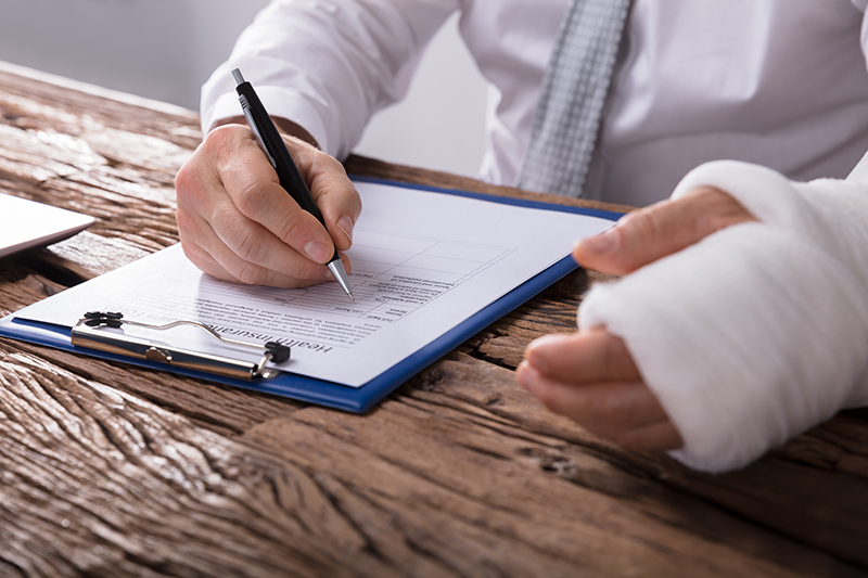 Close-up Of A Businessperson With Broken Arm Filling Health Insurance Claim Form On Wooden Desk