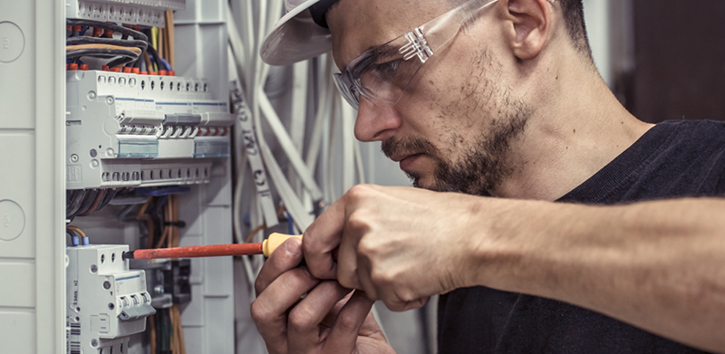 a male electrician - electrical contractor at work
