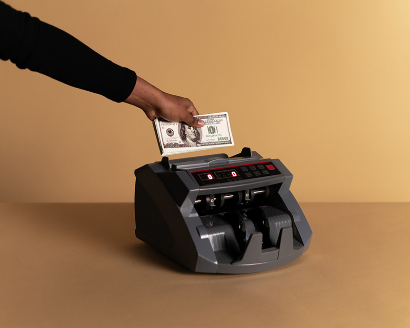 some one holding dollar bills over a money counting machine