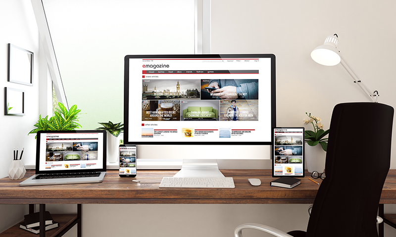 Web design on Computer and laptop screen on the top of wooden table