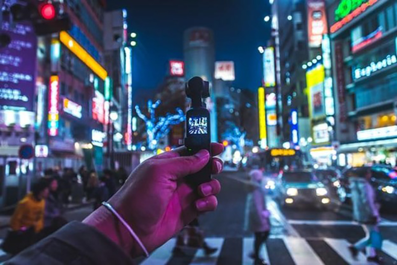 Man holding small black video cam on the street at night time