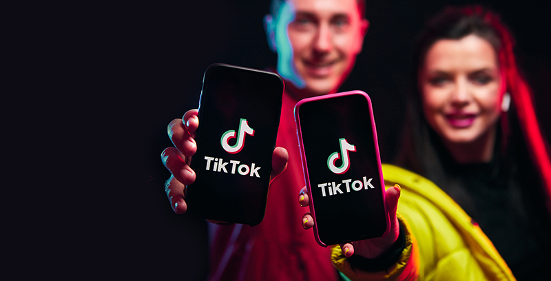 Young girl and boy (blogger) posing with smart phone and making video content in Tik Tok