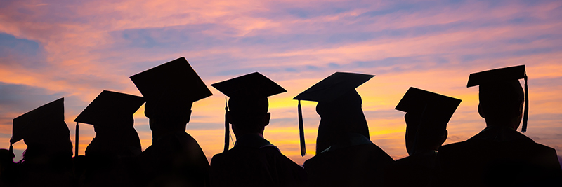 Silhouettes of students with graduate caps in a row on sunset background.