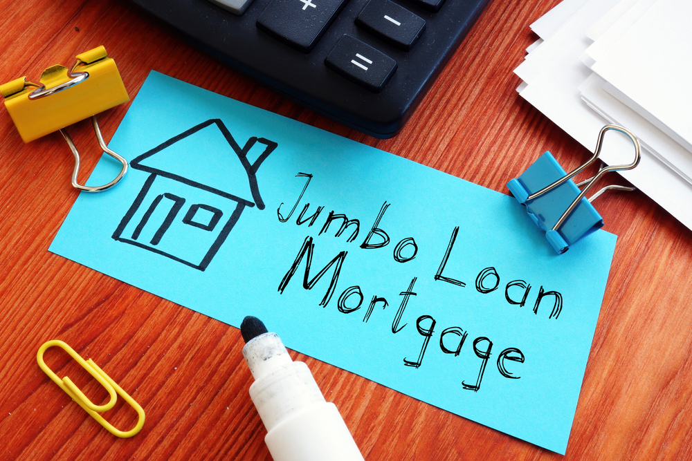 the words jumbo loan mortgage written on blue paper next to drawing of a house