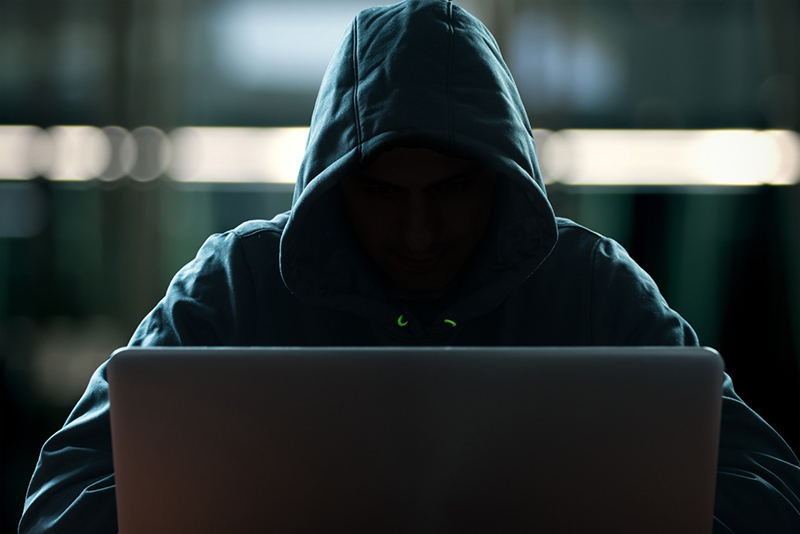 Person in black hoodie using laptop