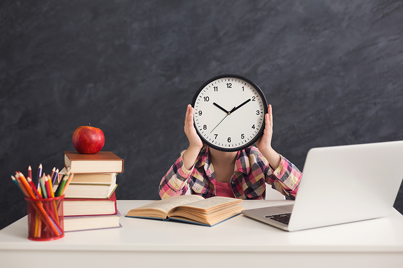 Girl sitting with stack of books and laptop, holding big clock, covering face