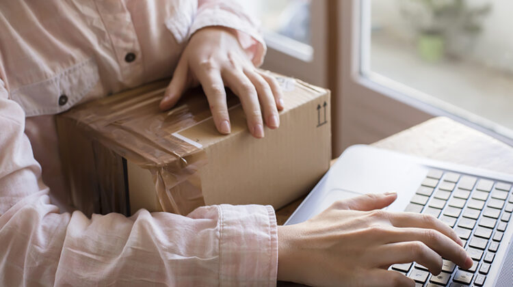 A close up of a female hand with a keyboard and a parcel, buying things on the internet