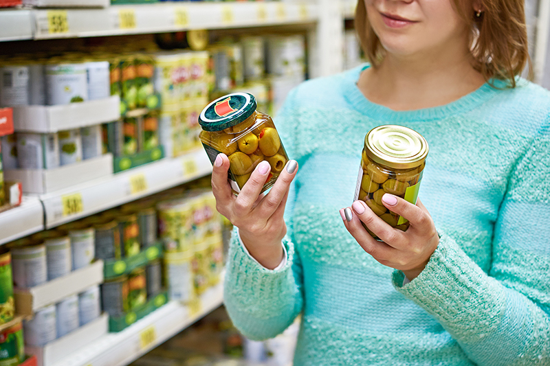 Woman reading the product label in the grocery