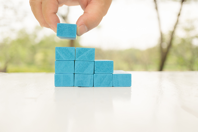 Man's hand holding blue wooden block on white wooden table.