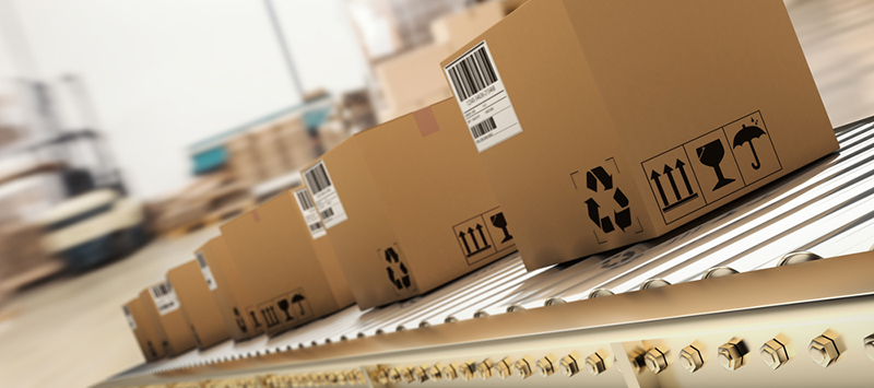 Packed products on production line in cardboard boxes in warehouse