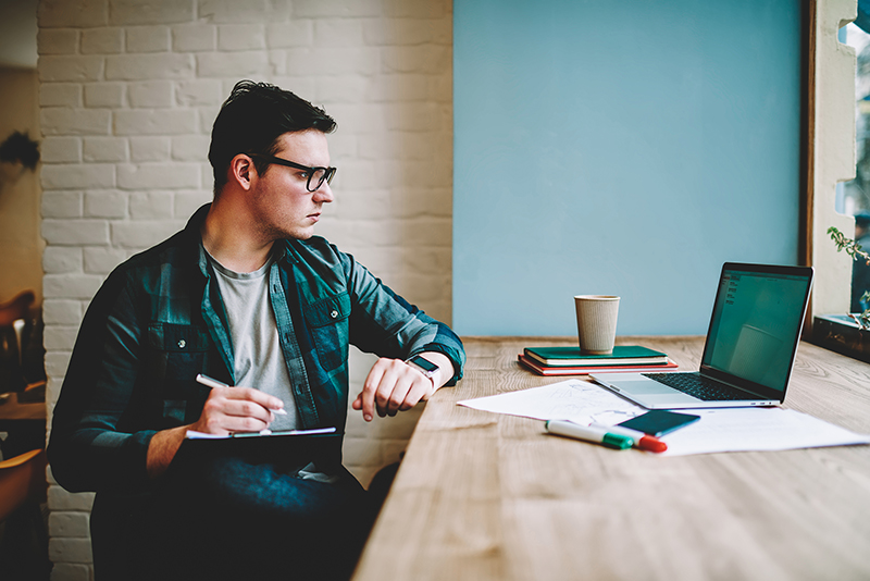Pensive hipster guy in eyewear watching training webinar on laptop computer spending time on e learning,