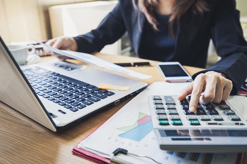 Woman using laptop and calculator for accounting