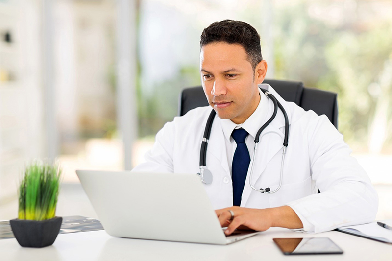 Doctor or medical consultant in white coat with and stethoscope sitting at a desk working on laptop
