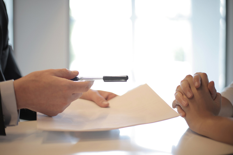 businessman giving contract to woman to sign