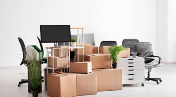 Carton boxes with stuff in empty room. Office move concept. Packing strategy