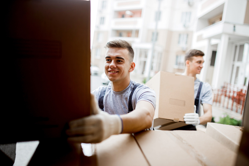 A young handsome smiling mover wearing uniform is reaching for to grab a box in removal van