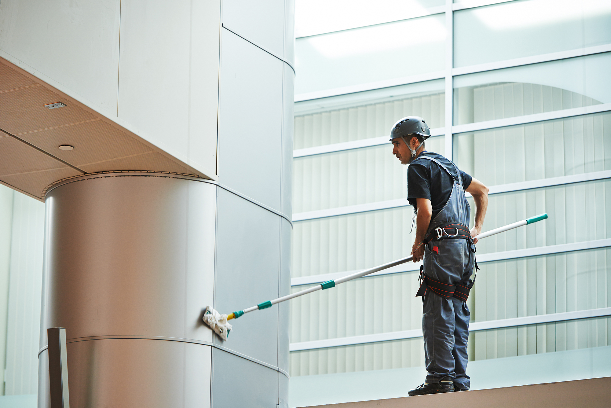 Man cleaning the wall inside the building