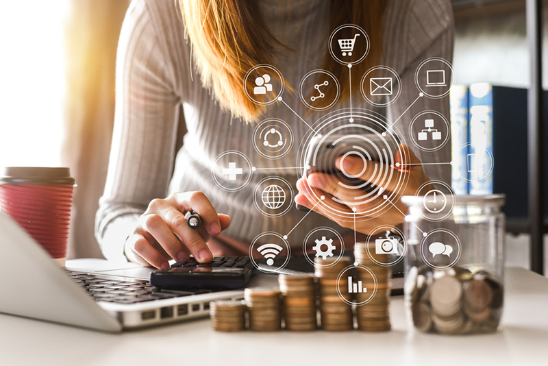 accountant working on desk in office using calculator and smartphone and laptop to calculate budget. concept finance and accounting with VR icon in morning light