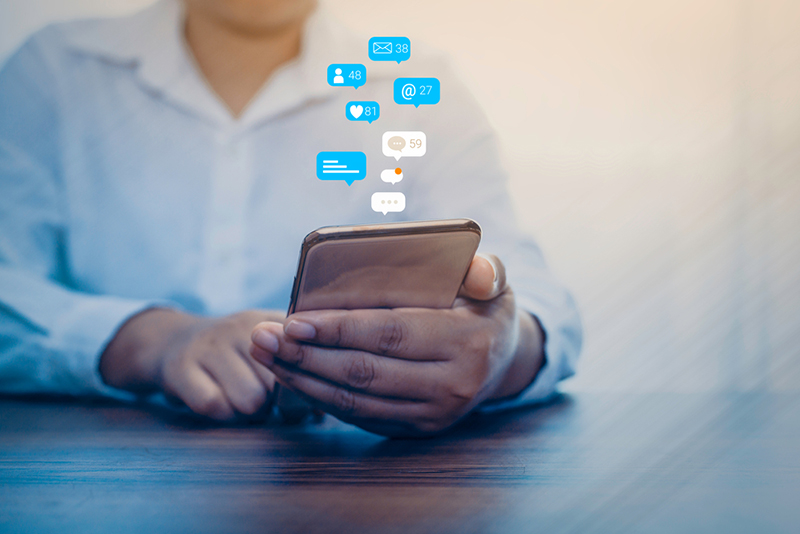 Person using a social media marketing concept on mobile phone with notification icons of like, message, comment and star above smartphone screen.