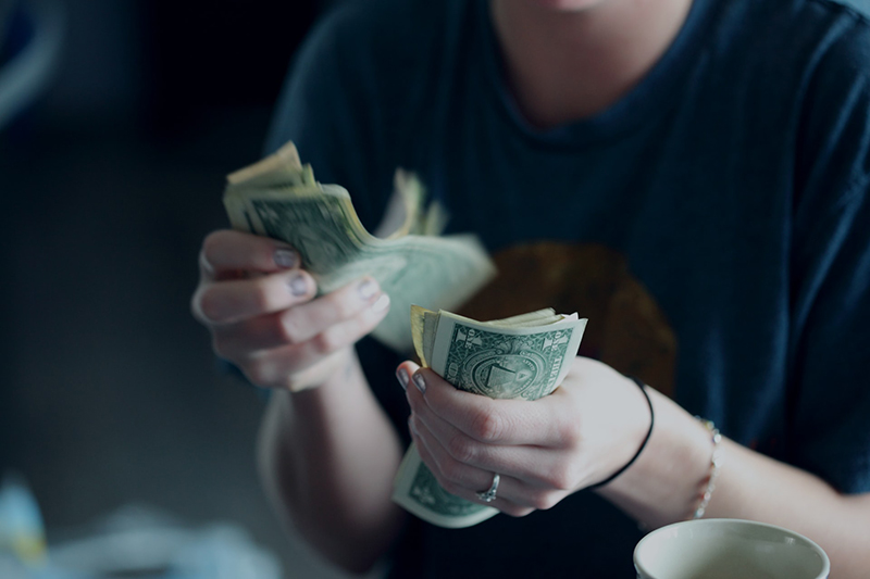 Person counting dollar banknotes
