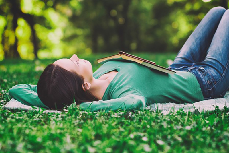 Female lying on her back on grass with a book on her chest