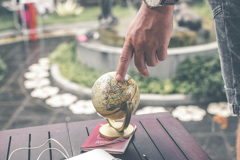 Person holding terrestrial globe scale