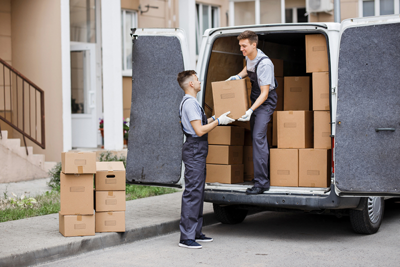 Two young handsome movers wearing uniforms are unloading removal van