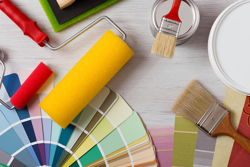Painter and decorator work table with house project, color swatches, painting roller and paint brushes,