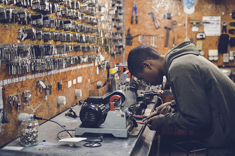 Young man working at work bench in key cutting shop