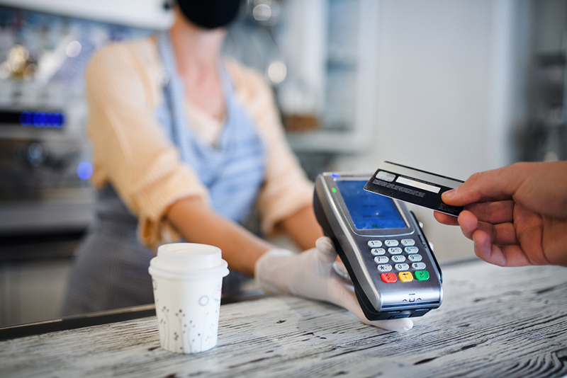 Contactless credit card transaction, coffee shop open after lockdown.