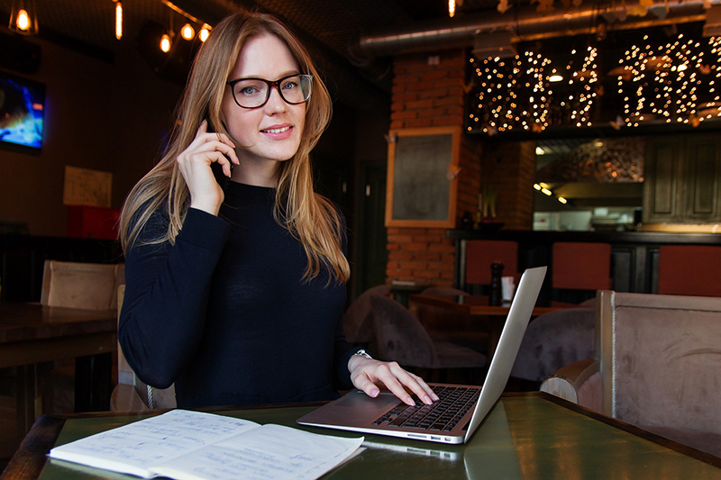 Successful business woman on the phone and working on laptop