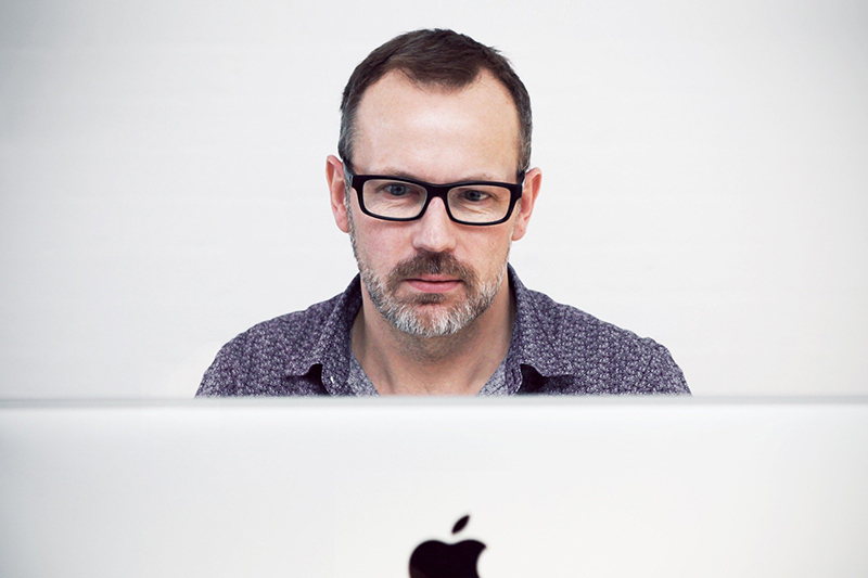 Man with hair loss working on iMac pro computer