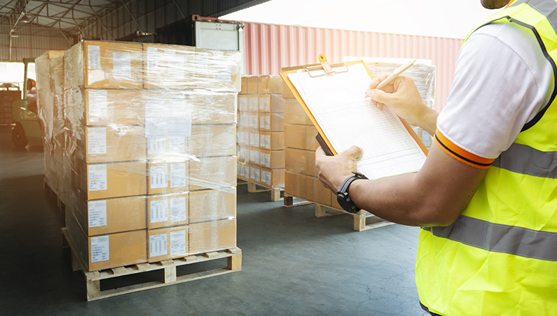 Man holding clipboard while checking items in a warehouse
