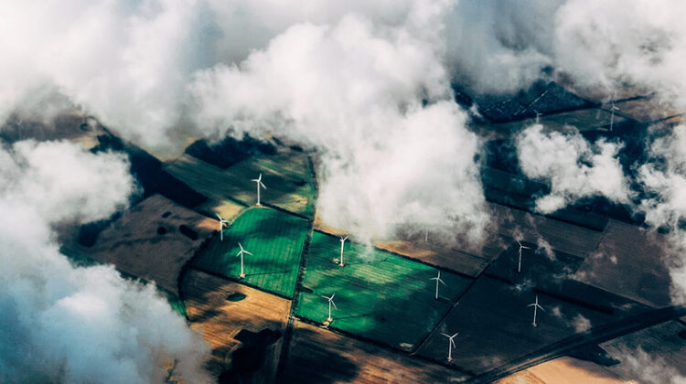 aerial view of windfarm through the clouds - green energy