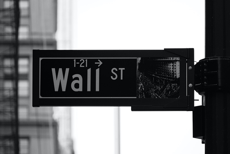 greyscale phot of Wall St. sign