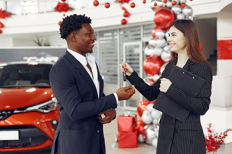 Young preety car loan agent handing the car key to her cclient