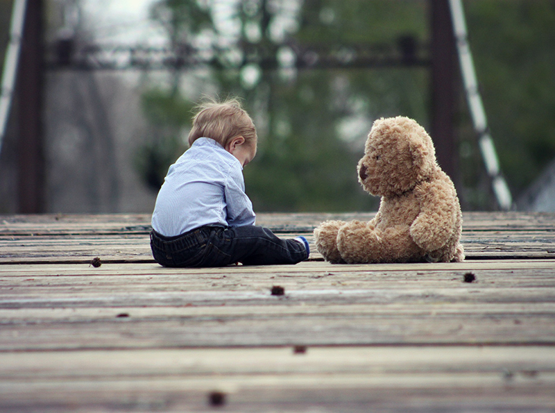 young boy sitting with brown bear plush toy on wooden bridge