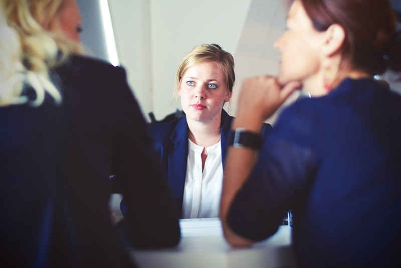 Woman in front of two women interviewer