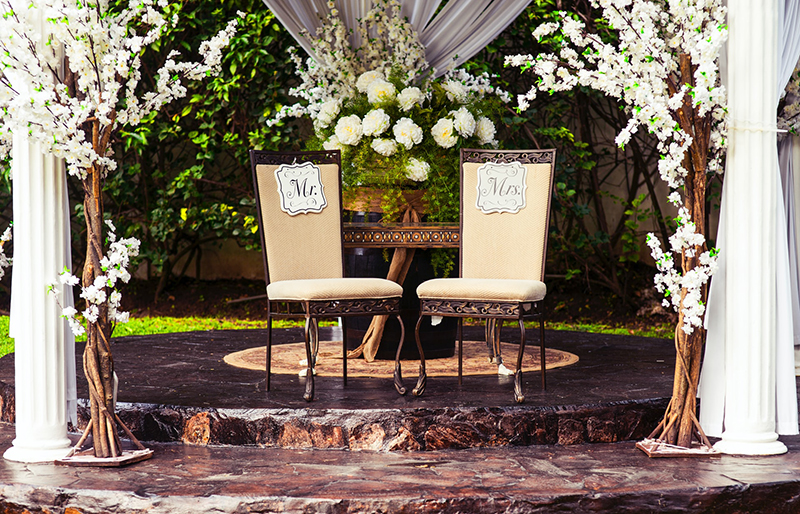 Wedding chairs for Mr and Mrs in outdoor setting with pillars and drapes